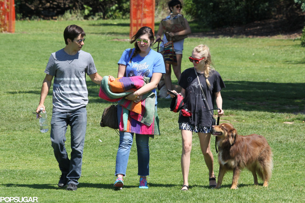 Amanda Seyfried and Justin Long walked on the grass with a friend.
