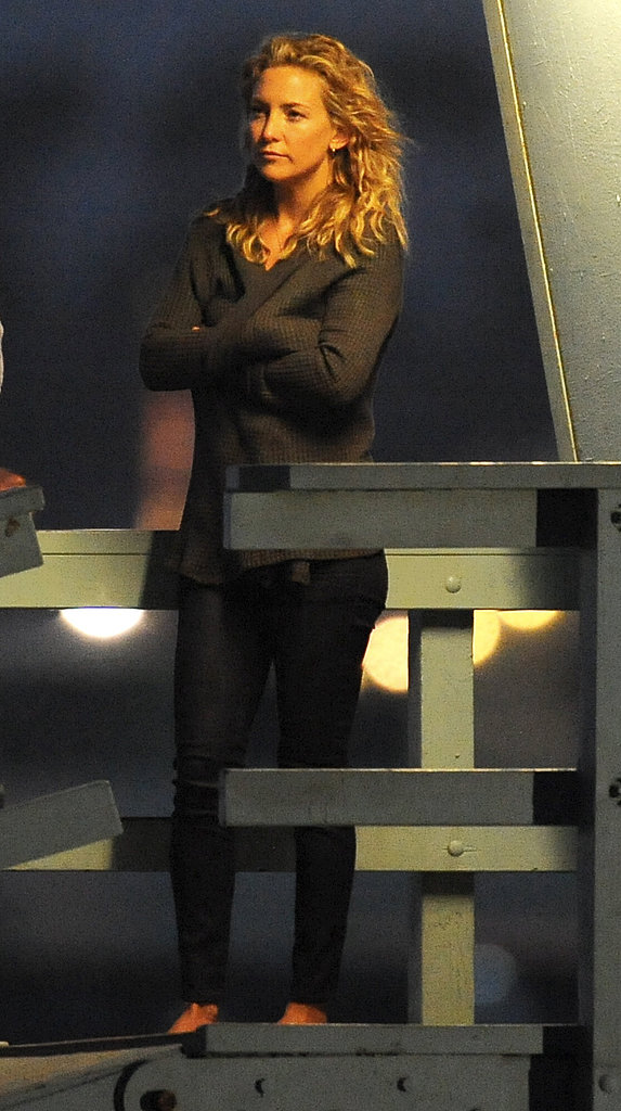 Kate Hudson kept herself warm in a sweater on set.