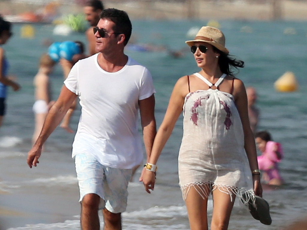 Pregnant Lauren Silverman covered her baby bump in a white dress to hit the beach hand in hand with Simon Cowell.