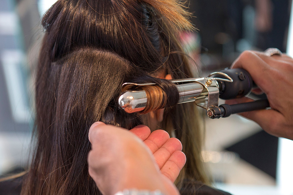 Once your hair has been smoothed out with the blow dryer, grab a large curling iron to form your waves. Start off by sectioning your hair at the nape of your neck and spray each section with a flexible hold hair spray like Kerastase Double Force ($39) for heat protection and hold. Then, wrap your hair around the iron, making sure to curl all the way to the end for an even curl.