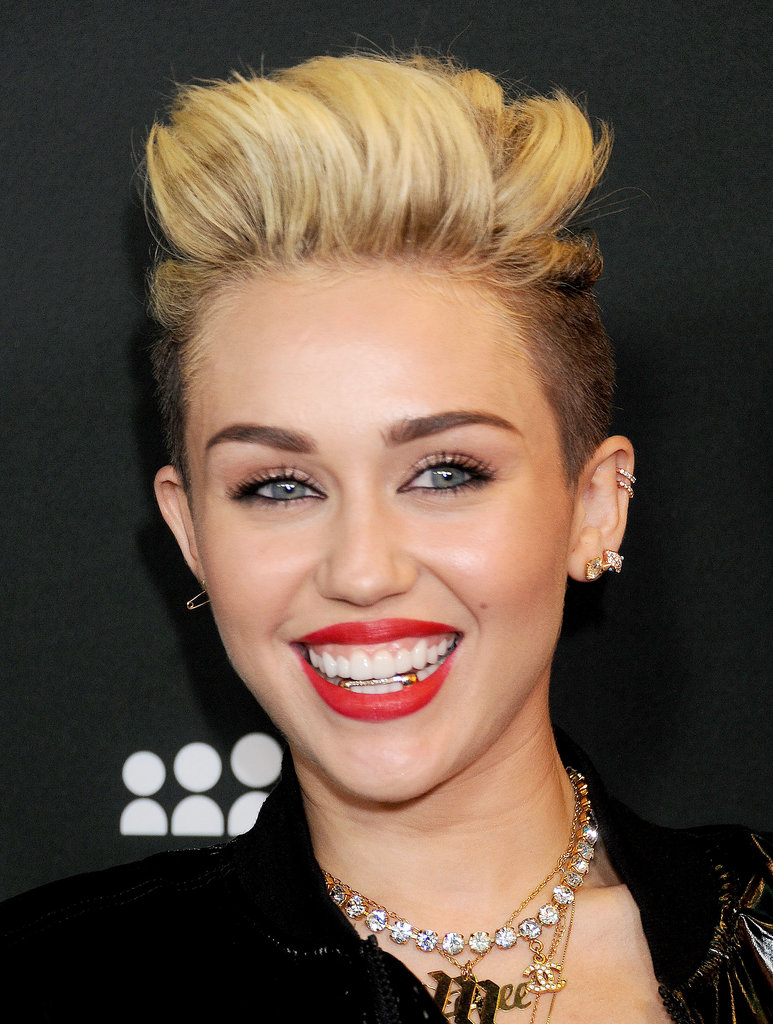 This Summer, Miley showed off her signature cherry-red lip color — and an edgy new grill.