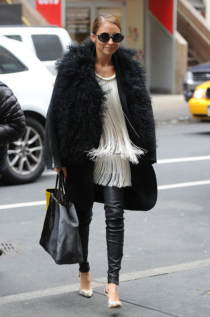 Nicole Richie combated the cool NYC temperature with lots of textured layers — a Mongolian fur jacket worn over a long coat, a fringe Stella McCartney blouse, and slick leather pants. She accessorized her cozy, yet chic, style with printed pumps, a colorblock Fendi bag, and cool-girl shades from her House of Harlow 1960 collection.