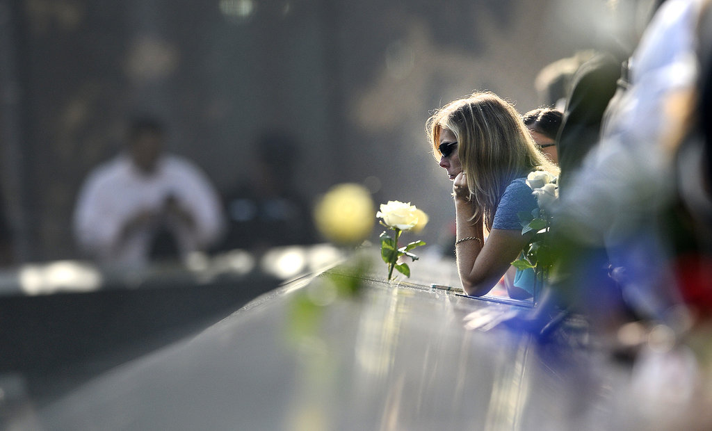 A woman reflected beside the 9/11 Memorial in NYC.