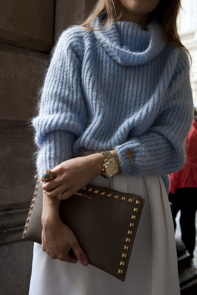 Gold studs and jewels glittered against her cozy sky-blue knit.