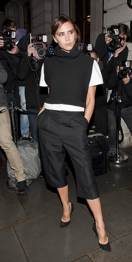Victoria Beckham accented her cropped black pants with a white tee, which she layered under a black cowl neck sweater at the British Vogue party.
