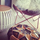 A sheepskin-covered butterfly chair paired with a Moroccan patchwork pouf and a low round side table complete a relaxed vibe. Source: Instagram user tarjasnowland