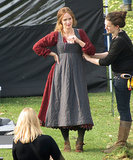 Emily Blunt hid her growing baby bump in her Into the Woods costume while filming on Wednesday in the UK.