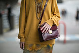 A killer color combo, thanks to her canary yellow knit and deep cranberry bag.