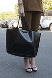 An ultrasleek Givenchy tote in hand.