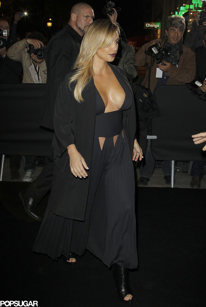 Kim Kardashian left little to the imagination when she chose a black gown with a cleavage-baring neckline and burgundy lips for the Mademoiselle C premiere during Paris Fashion Week.