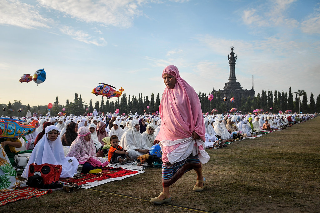A woman walked beside the crowd as people gathered for Eid al-Adha in Bali.