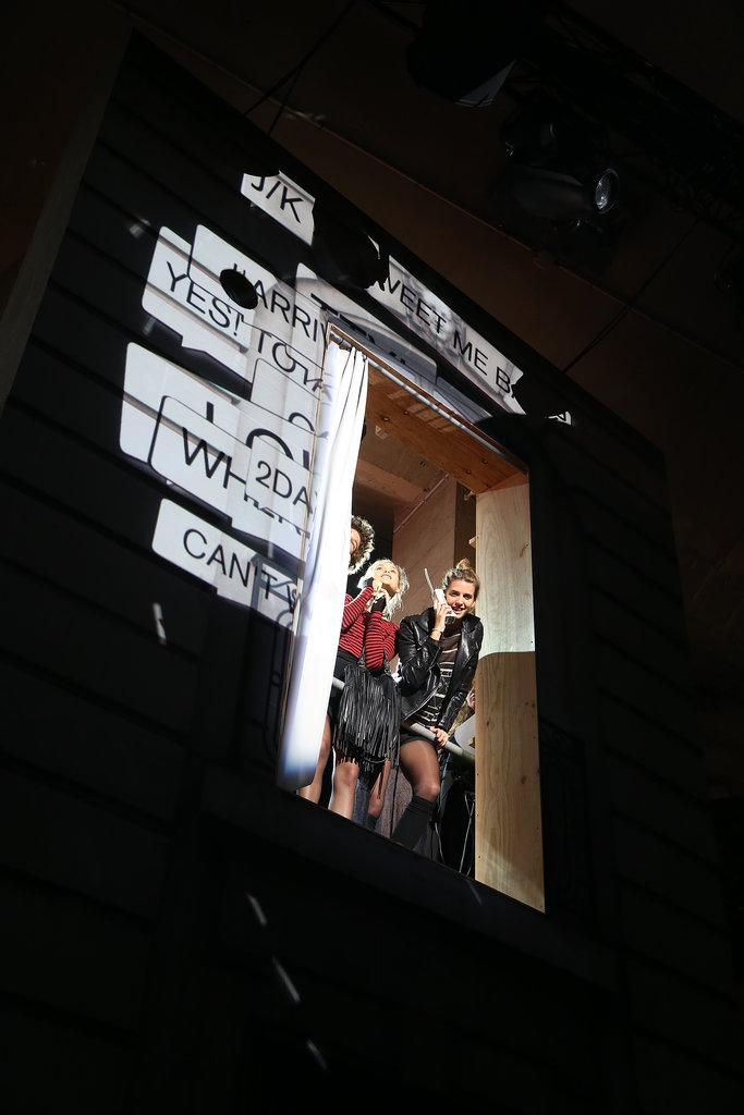 Models first appeared in second-story windows above the street scene as they made plans for a night out together.  Photo courtesy of H&M