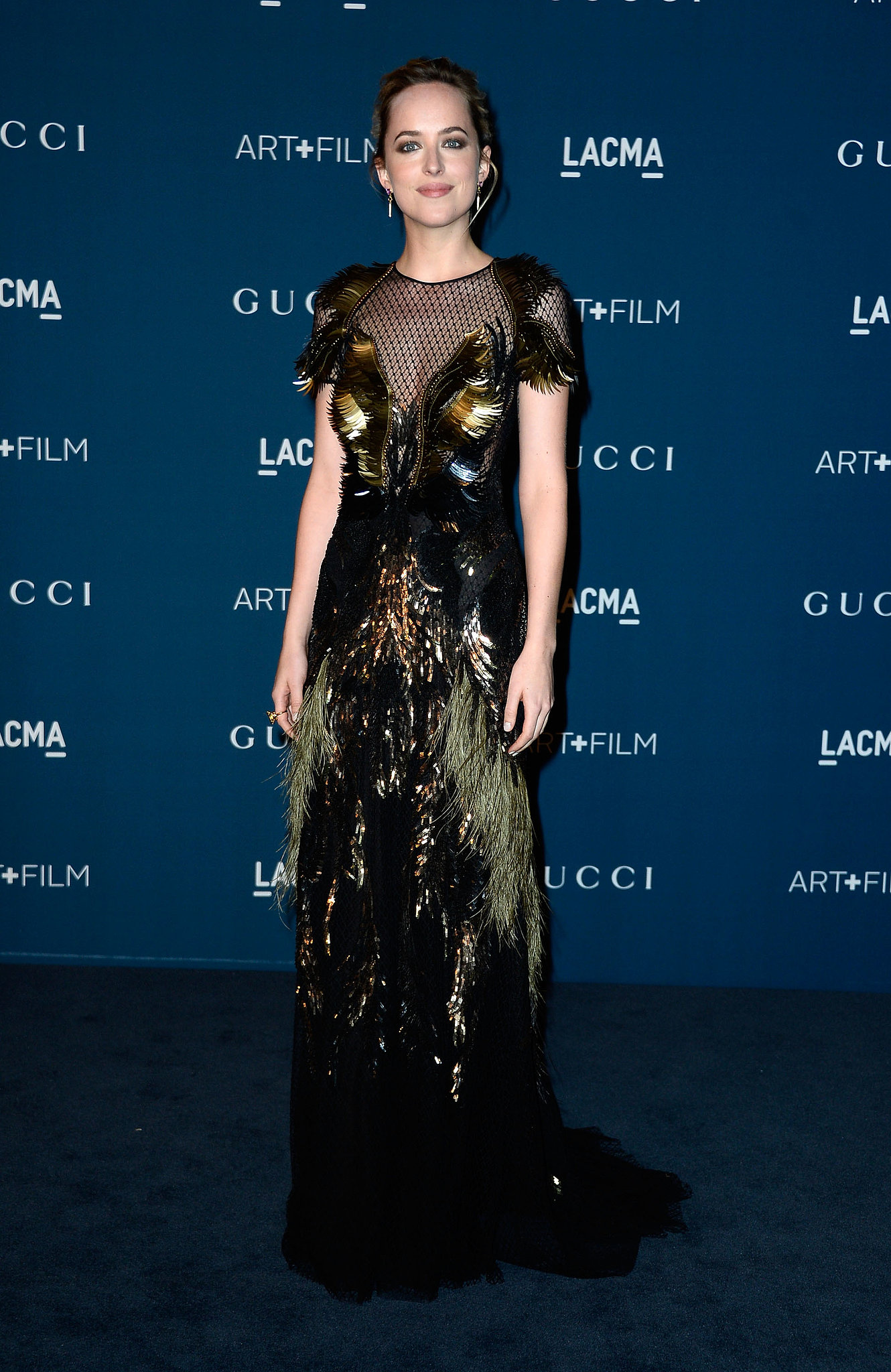 Dakota Johnson wowed in her rich green gown while walking the carpet with Gucci at LACMA.