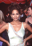 The wispy face-framing pieces. The heavy lip liner. The piecey updo. We can't imagine a more '90s look on Halle Berry.