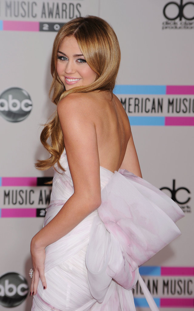 Miley Cyrus wore a light-pink dress and gold body glitter in 2010.