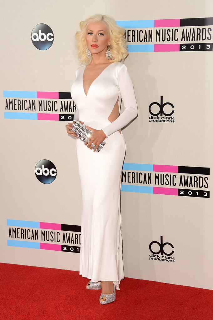 Christina Aguilera oozed retro glamour in a long-sleeved white Maria Lucia Hohan dress with strategically placed cutouts, a sparkling box clutch, Lorraine Schwartz flower rings, and peep-toe Jimmy Choo pumps.