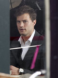 Jamie Dornan channeled Christian Grey while filming the coffee shop scene with Dakota Johnson on the set of Fifty Shades of Grey in Vancouver on Sunday.