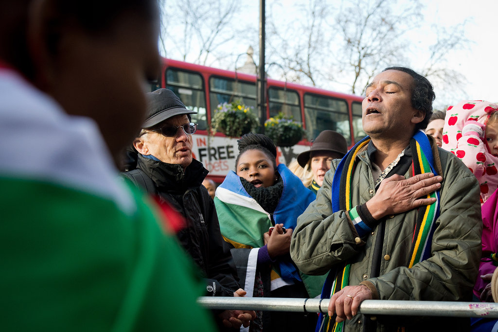 A man in London, England, honored Nelson Mandela with a hand over his heart.