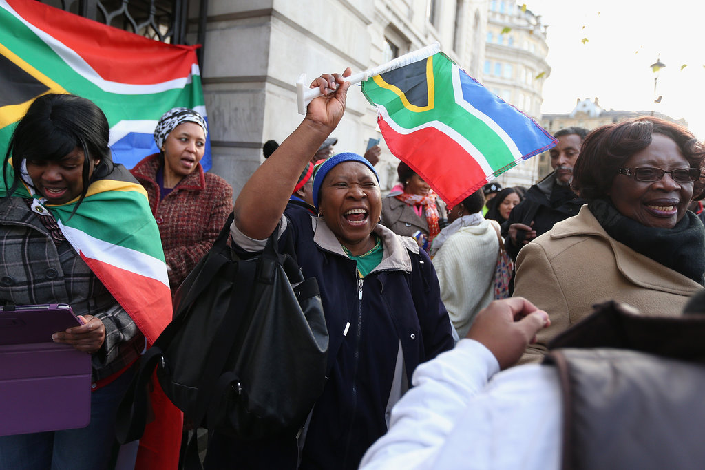 People sang in tribute outside London's South African embassy.