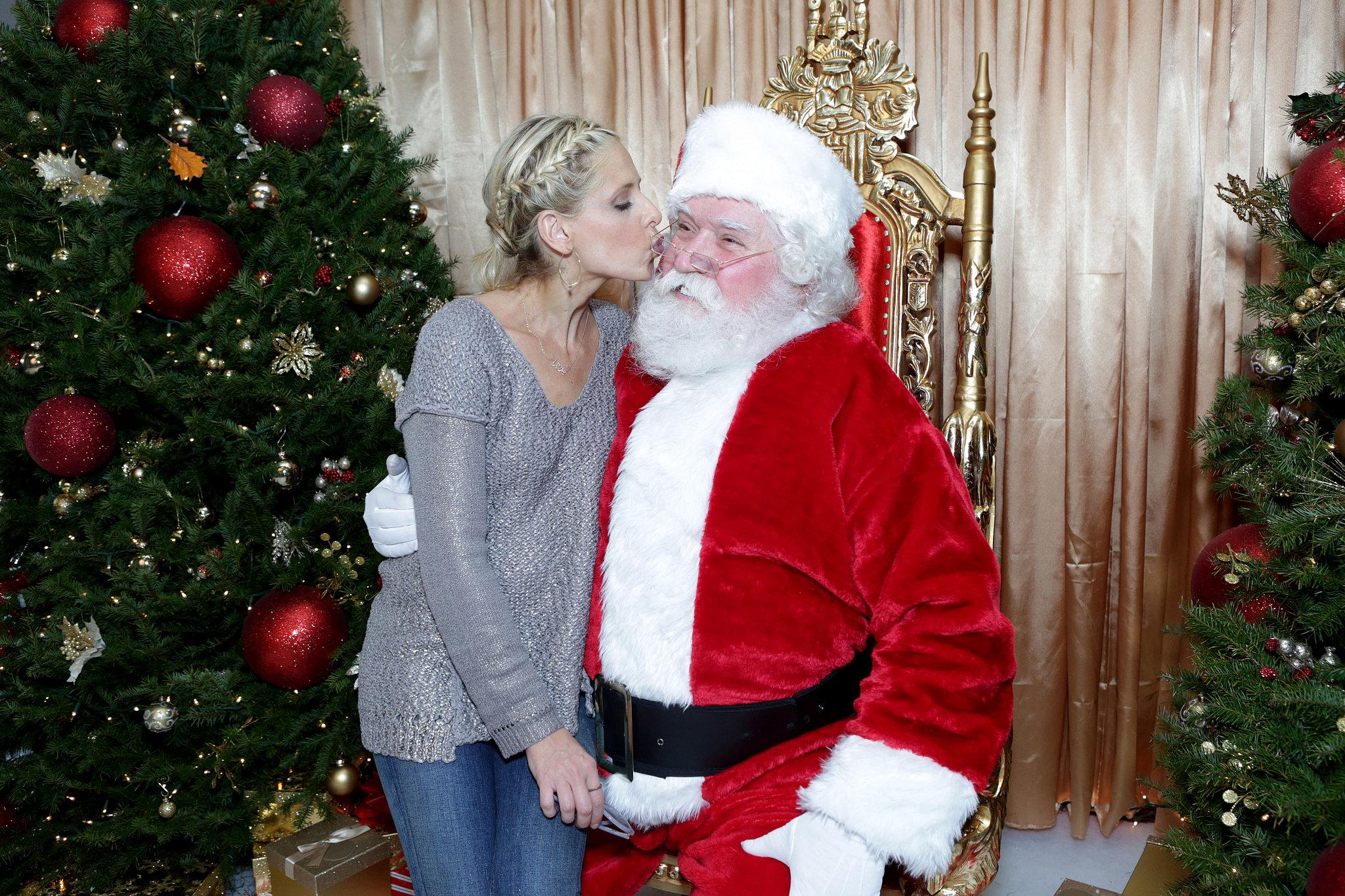 Sarah Michelle Gellar puckered up to Santa Claus at his Secret Workshop benefit in LA.