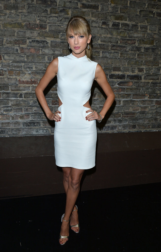 Swift balanced the open back and sexy side cutouts of her little white Calvin Klein Collection dress with a high collar, demure hemline, and flirty ponytail at the Toronto International Film Festival.