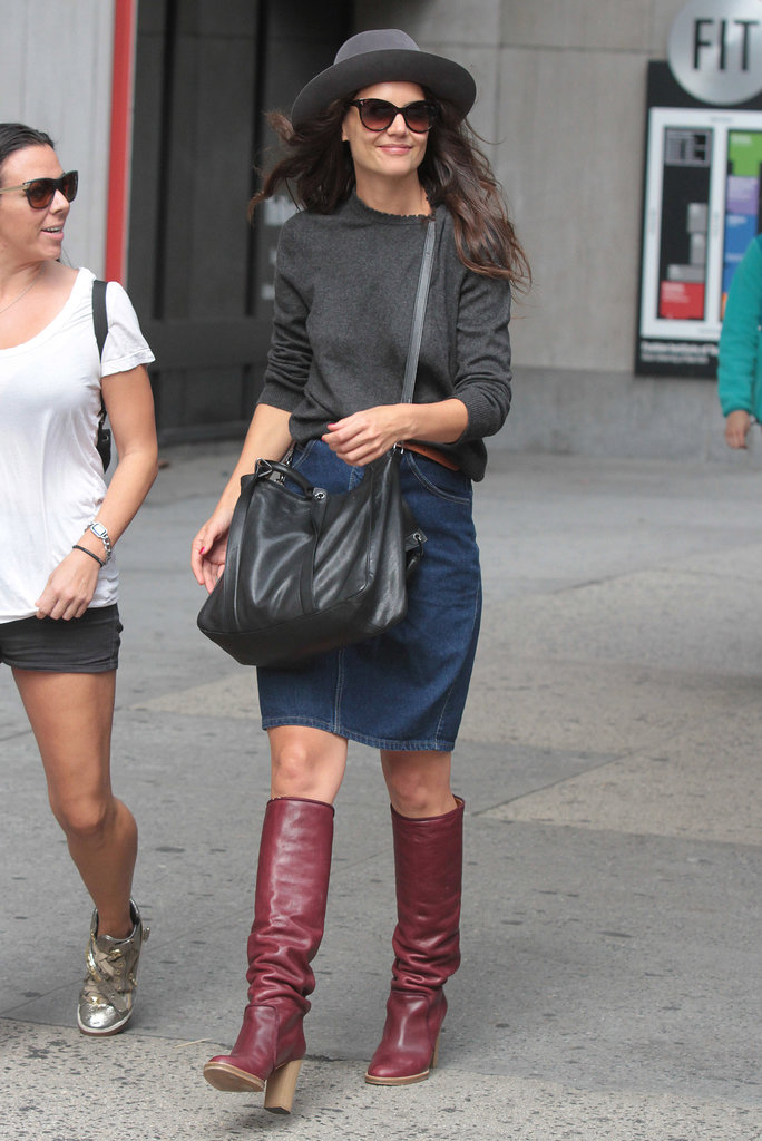 A cozy sweater, denim skirt, and below-the-knee red leather boots combined for a street-chic style in September 2013.