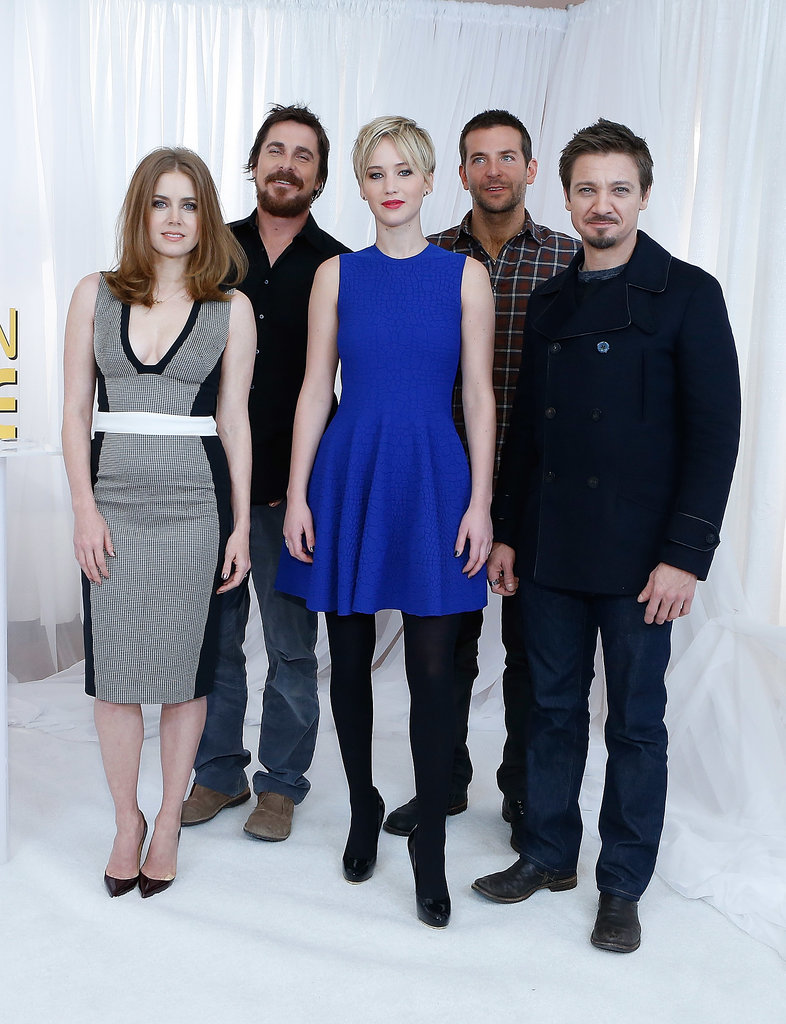 Jennifer Lawrence stunned during the American Hustle cast photocall in NYC, posing for pictures in a bright blue dress alongside her castmates.