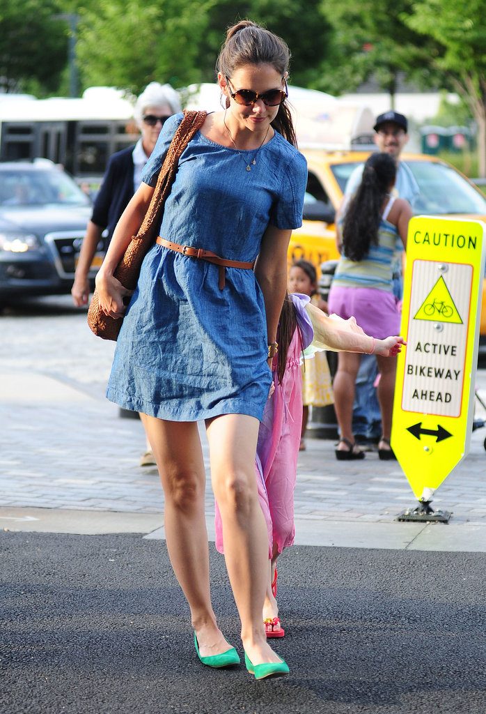 While spending time with Suri in NYC, Katie exuded daytime chic in a Madewell denim short-sleeved dress cinched with a skinny tan belt and emerald flats in July 2012.
