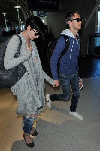 Anne Hathaway headed out of LAX in boyfriend denim and a cozy wrap with husband Adam Shulman at her side.