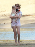 On Thursday, Anne Hathaway kissed a baby while walking on the beach in Hawaii with friends.