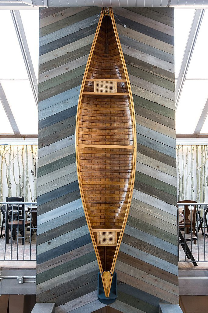 Our favorite feature of the space, an old canoe, is used as art against the chevron wood paneling.  Photo by Michael Friberg via Airbnb