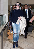 Anne Hathaway kept cozy in a navy sweater and pair of distressed jeans. And to break up all that blue? A brown suede tote, aka the perfect carry-on.