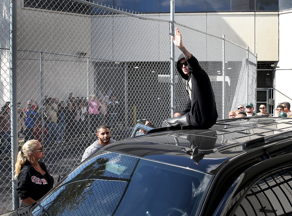 Justin Bieber left the Miami-Dade County jail in Florida on top of his black SUV while waving to gathered fans.