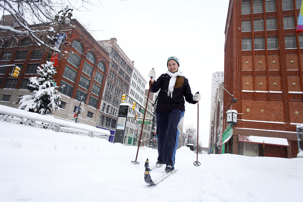 A woman skied through the snowy streets of Detroit, MI.