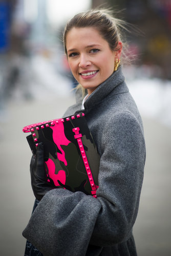 Helena Bordon lit up a gray coat with a neon and camo-printed Valentino clutch.