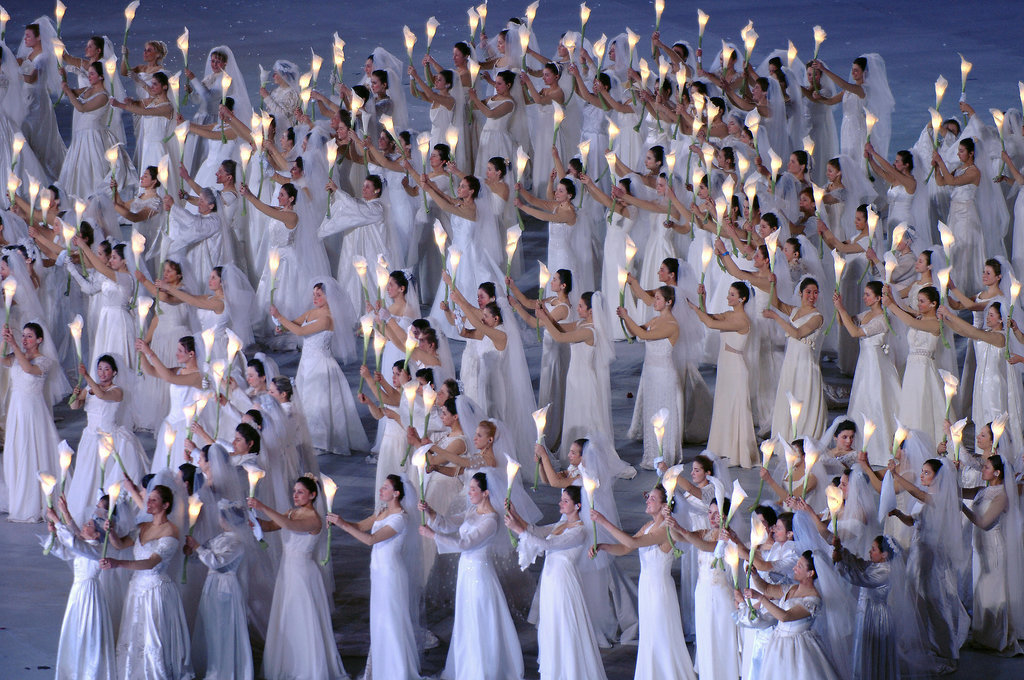 "White maidens carried lit-up lilies while forming the ""Dove of Peace."""