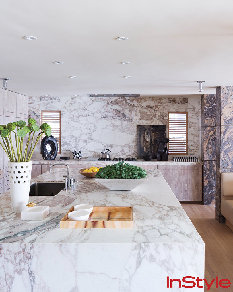 To optimize the ocean view, the kitchen and eating nook are elevated. Bleached walnut floors and marble-paneled walls frame the space. The island (and no doubt focal point) is rain-forest marble. The cabinets are made of bleached Douglas fir.  Photo by Dean Kaufman for InStyle
