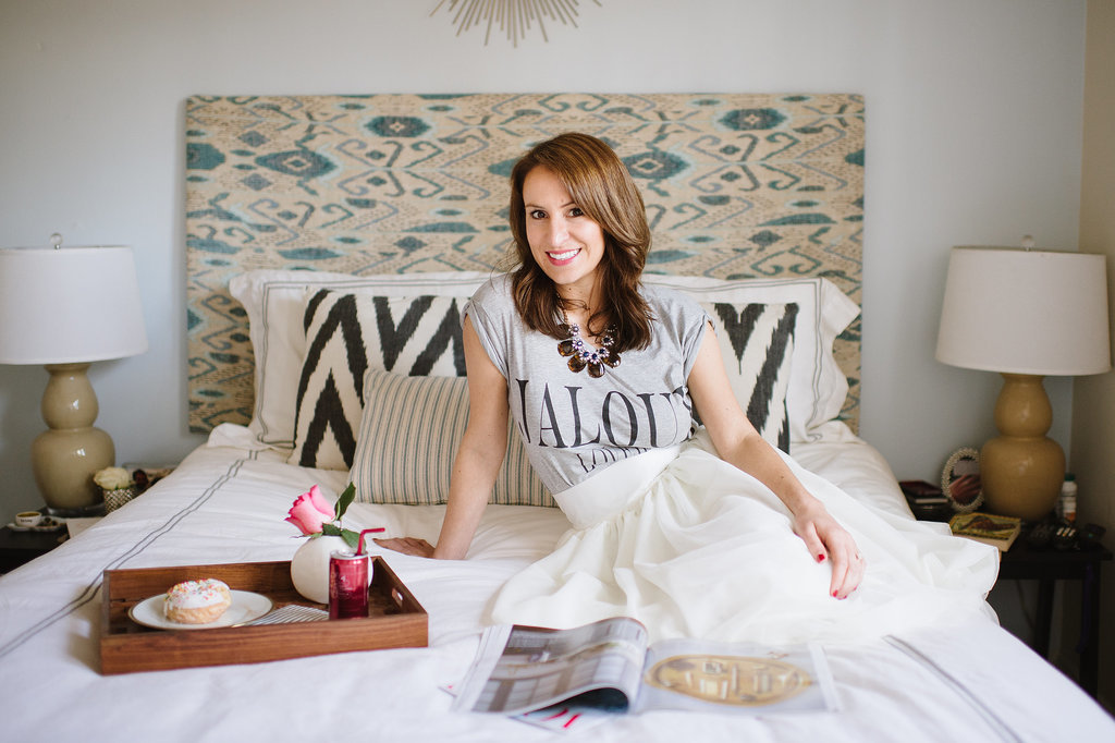 Caitlin's bedroom is a great example of chic design on a budget. She DIYed her headboard and shopped at Target for her bedding and starburst mirror.  Source: Natalie Franke
