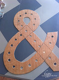 We started with quarter-inch chip board. Curt drew the ampersand then cut it out using a jigsaw. We drilled 3/4 inch holes for the lights. At first we had 1/2 inch holes, then realized they were too small and had to make them bigger. That's why more than a few of them are mangled; I was struggling. Source: Happy Looks Good on You