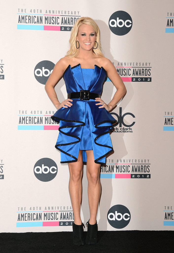 For the 2012 American Music Awards, Carrie swapped her lacy Abed Mahfouz gown for a cobalt origami-style Sarli Couture dress while posing in the press room.