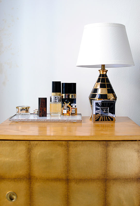 . . . While black-and-gold lamps and a tray filled with perfume add glamour to her nightstand.   Source: Homepolish
