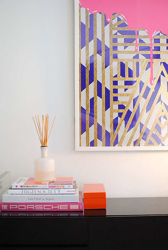 A colorful graphic and a stack of coffee-table books lay the foundation for smaller accessories like a sculptural air freshener and a lacquered box.    Source: Homepolish