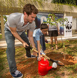 He helped kids plant trees at an environmentally progressive school in Singapore in March 2014.
