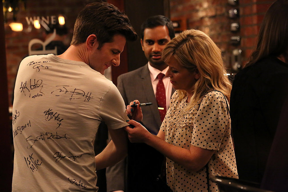 Some girl signs Ben's shirt.