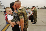US Marine Staff Sergeant Chris Carlson kissed his wife, Kasie, as she held their 21-month-old son Ryan during the homecoming of Helicopter Squadron 466 from Iraq on July 22, 2003, at Miramar Marine Corps Air Station in San Diego, CA. His squadron's routine six-month deployment became more than a year spent overseas due to the war in Iraq, making it one of the longest deployed units in the Marine Corps.