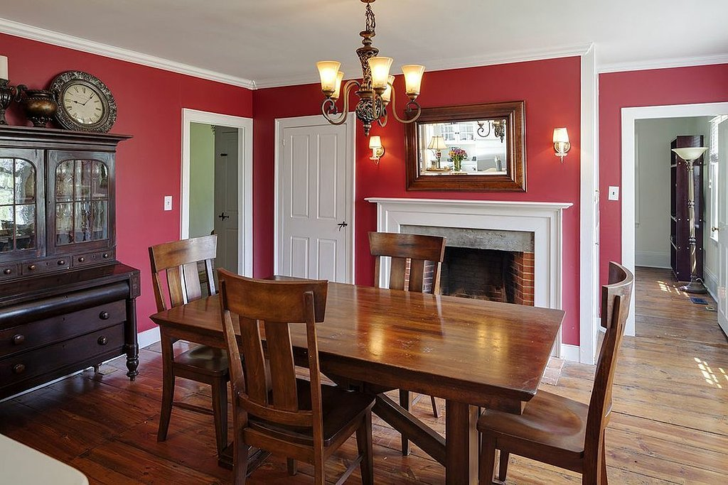Red walls and an antique hutch are just a few of the classic elements in the dining room.  Source: Landvest