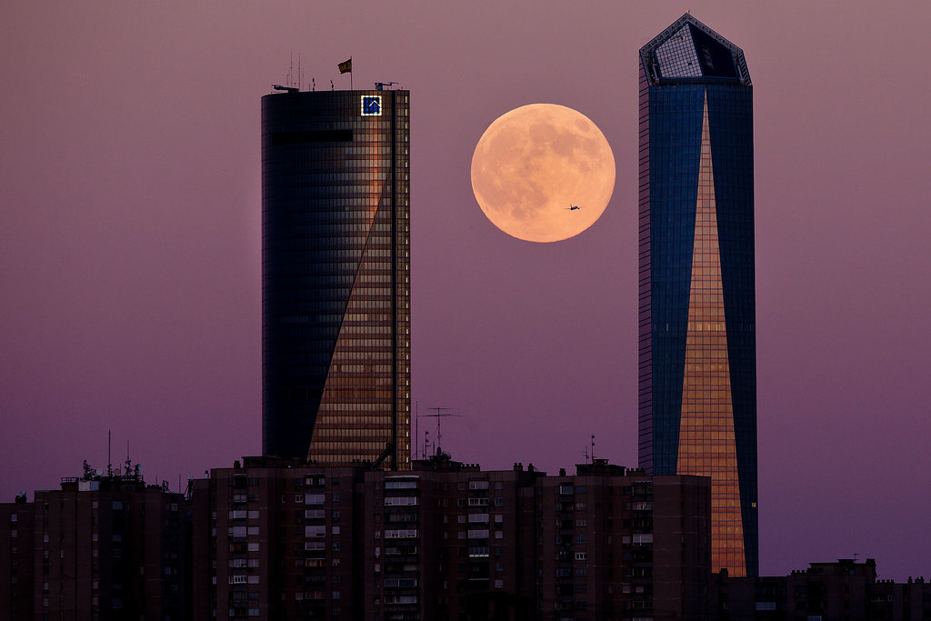Here, a plane flights across the supermoon in between two Madrid skyscrapers on Aug. 10.