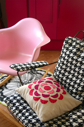 A bubble gum pink rocker is muted by the masculine houndstooth pattern on the chair next to it.  Source