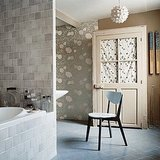 Gray doesn't always need to be sober — it can be playful, too. By balancing gray patterned wallpaper with silver ceramic bath tiles of varying shades and simple gray floor tiles, you'll show that gray has many faces. Feminine flowers, mottled rectangles, and diamond patterns all work together in this space. Source