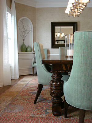 A warm-colored rug is offset by cooler colors in this formal dining room's chairs and vases. It is absolutely appropriate to mix and match! Source
